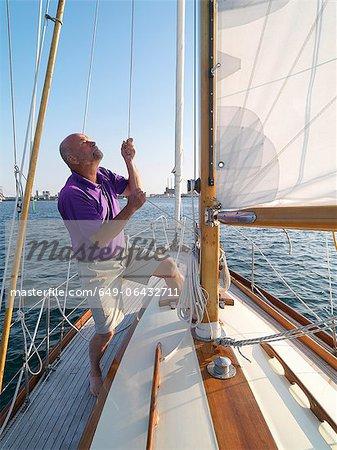 Man adjusting rigging on sailboat