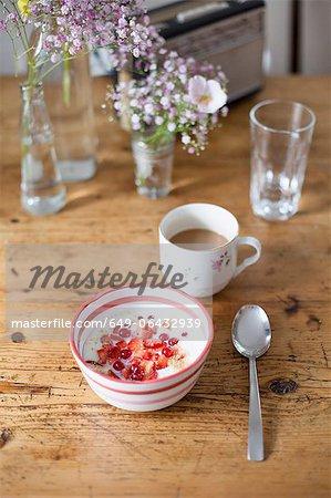 Bowl of fruit and yogurt with coffee