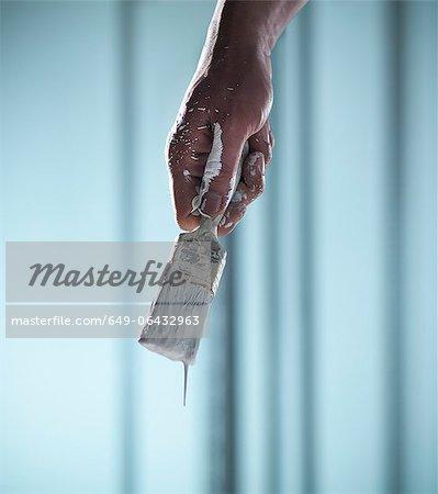 Close up of hand holding paintbrush