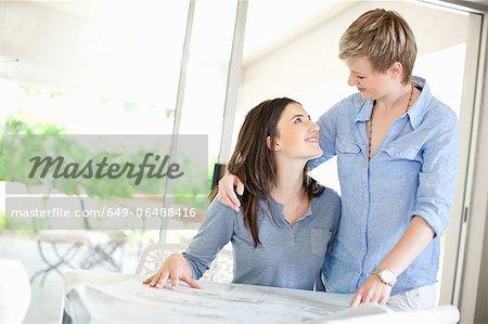 Lesbian couple reading blueprints