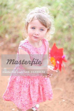 Girl holding pinwheel on dirt road