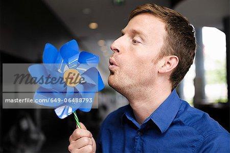 Man blowing pinwheel indoors