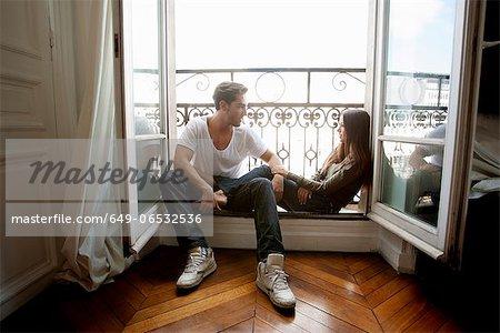 Couple sitting in windowsill