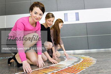 Businesswomen examining paint swatches