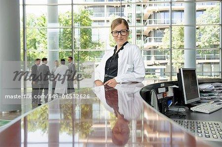 Doctor leaning on secretarys desk
