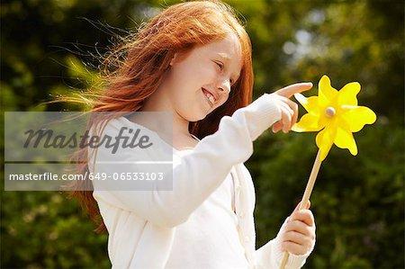Girl playing with pinwheel outdoors