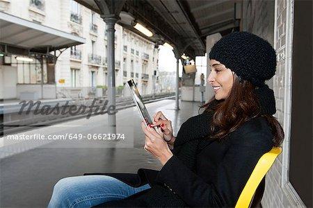 Woman using tablet computer on platform