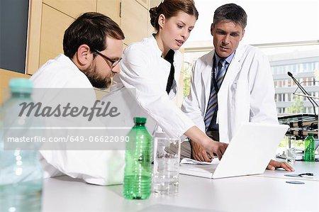 Doctors using laptop at desk