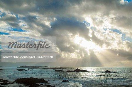 Sun shining through clouds over beach