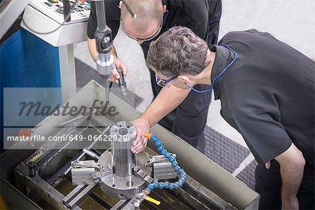 Workers examining steel rod in factory