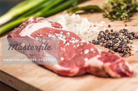 Close up of seasoned meat on board