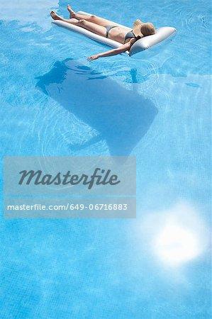 Woman laying on raft in swimming pool