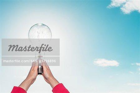 Woman holding light bulb in sky