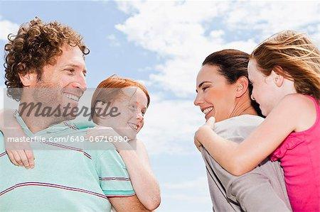Parents carrying daughters piggyback