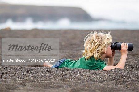 Boy using binoculars on beach