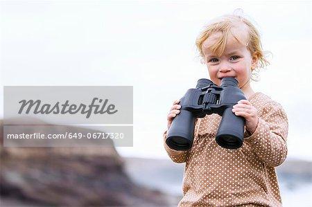 Toddler girl using binoculars on beach