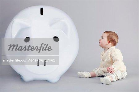 Baby girl examining large piggy bank
