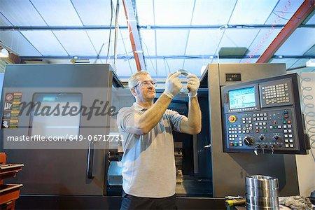 Engineer examining part in factory