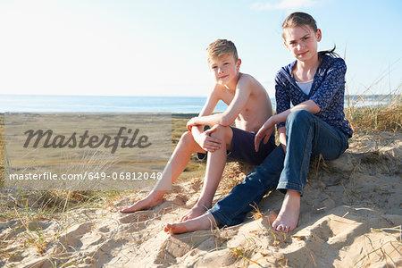 Boy and teenage girl sitting on beach