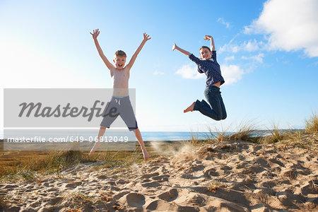 Boy and teenage girl jumping on beach
