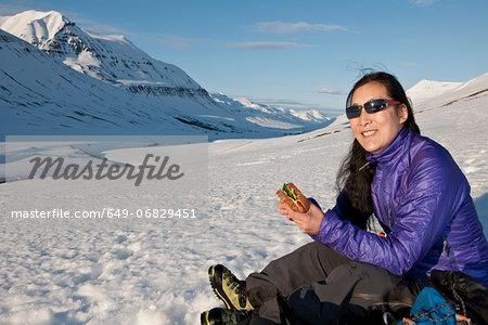 Mature woman enjoying sandwich in snow covered mountains, Skidadalur, Dalvik, Iceland