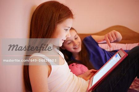 Girls using digital tablet together in bedroom