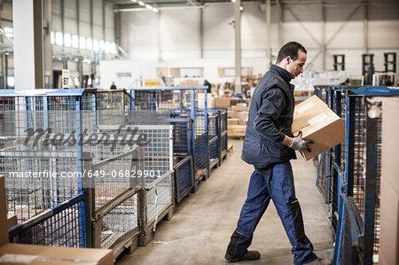 Male warehouse worker lifting cardboard box onto distribution trolley