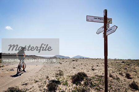 Man mountain biking past sign post, Lanzarote