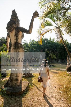 Woman walking past statue, Xieng Khu, Vientiane, Laos