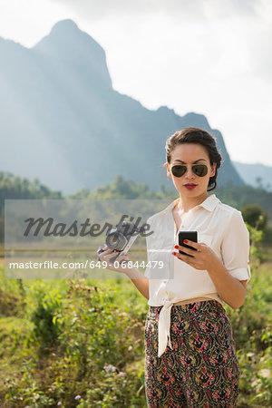 Woman using smartphone, Vang Vieng, Laos
