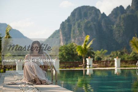 Woman sitting reading by swimming pool, Vang Vieng, Laos