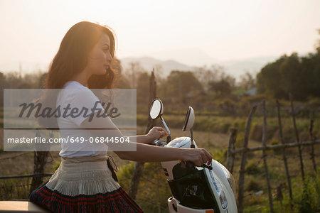 Woman on moped in rural scene