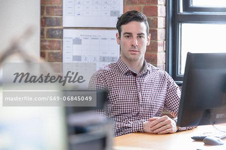 Office worker sitting at desk, portrait
