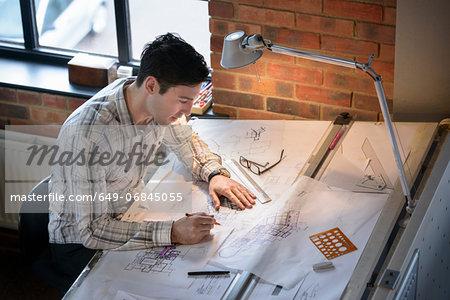 Architect drawing plans at drawing board