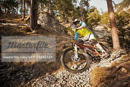Man mountain biking on rocks