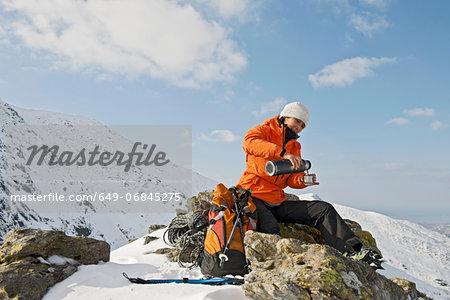 Female climber taking a coffee break on rock, Castell y Geifr, Snowdonia