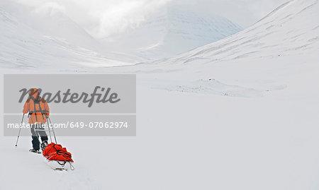 Woman pulling sledge in snow, Skidadalur, Dalvik, Iceland