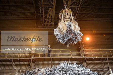 Steel workers watching mechanical grabber in steel foundry