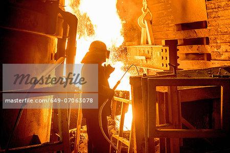 Steel worker in front of furnace fire in steel foundry