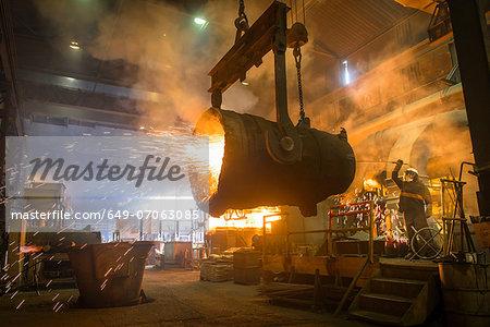 Steel worker and bucket of molten metal in steel foundry