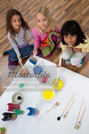Portrait of three girls painting on floor