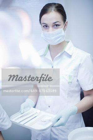 Portrait of female dental nurse holding surgical tray