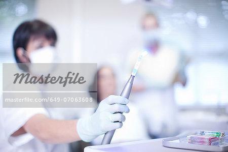 Close up of dentists hand holding ultraviolet light