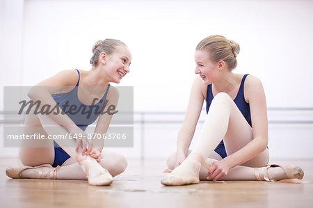 Two ballerinas chatting whist fastening ballet slippers