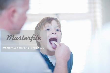 Doctor checking boys throat