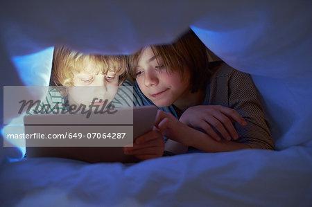 Brothers underneath duvet using digital tablet