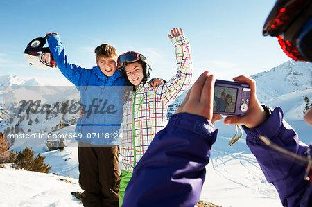 Girl photographing siblings, Les Arcs, Haute-Savoie, France