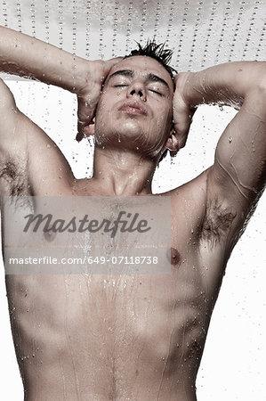 Young man showering, studio shot
