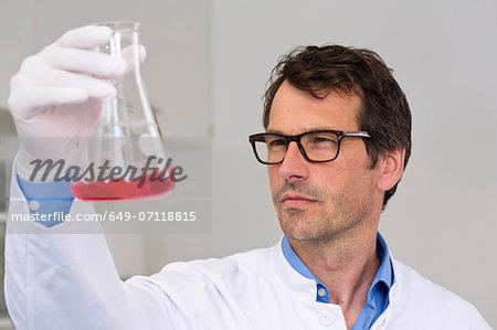 Male scientist examining ph-reaction of liquid in flask