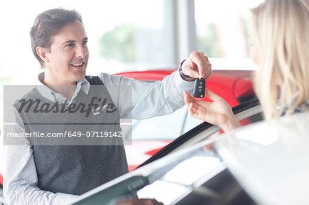 Car salesman handing keys to young woman in showroom